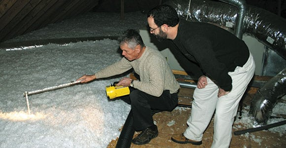 Bud Cole, left, Gibson Electric Membership Corporation residential energy services specialist, examines a member's attic insulation. Maintaining adequate insulation levels helps save energy — and money — year-round.