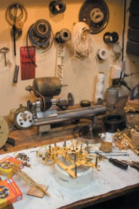 Shining brass internals of Howell Rust's latest project sit in his workshop. Rust uses his grandfather's tools when repairing clocks.