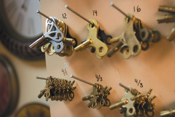Clock keys of different sizes hang on a showroom wall of Northside Clocks.