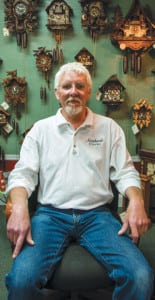 Howell Rust sits in front of an array of cuckoo clocks, the style his grandfather used to teach him the craft of horology.