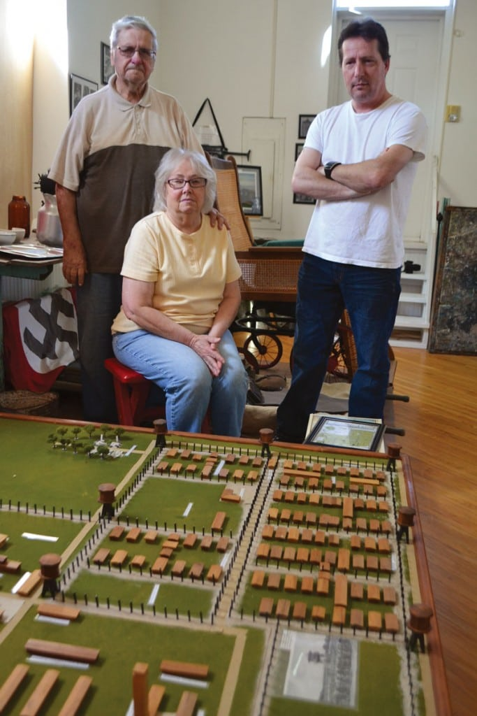 From left, Robert, Nita and Sean Boring, who collectively run the Military Memorial Museum, show a model of the POW camp created by many volunteers in Crossville. Photograph courtesy of Tennessee History for Kids