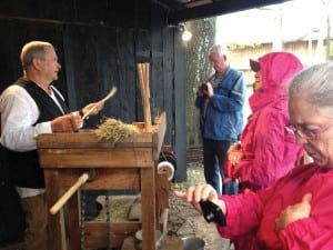 Visitors witness broom-making at a living history demonstration.