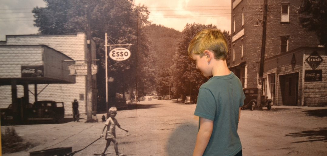 A young visitor to the Butler Museum waves to the photo of a boy named Russell Mink pulling his wagon through Butler in 1947. (Tennessee History for Kids photo)