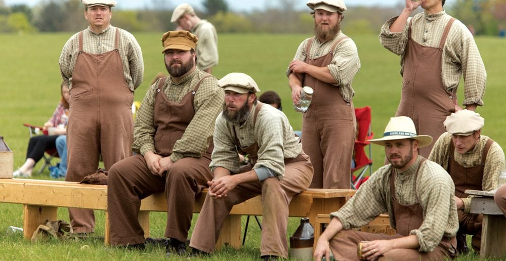 Distiller teammates watch during a rare break in the action. Vintage base ball is known for its good-natured camaraderie, with ballists even cheering on their opponents and complimenting them on good plays.