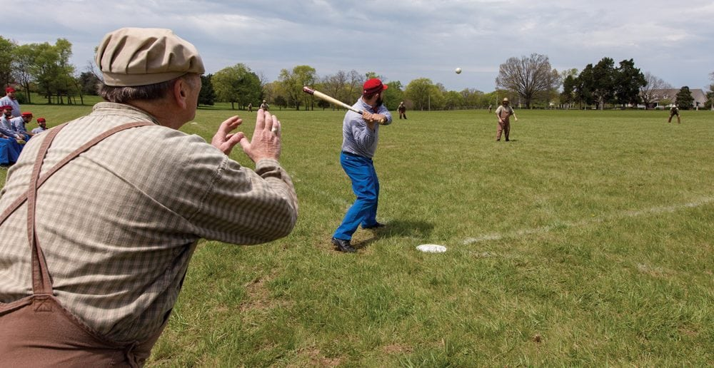 """A Lightfoot ballist is at bat as Distiller Rick """"Big Red"""" Brooks catches. Each vintage bat is hand-crafted by Smacker Bats of Murfreesboro. The company has been making bats according to early base ball specifications for 20 years."""