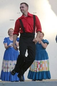Nathan Horton demonstrates buck dancing, a freestyle clog, during a performance by the Cripple Creek Cloggers. His wife, Carey, and Ann Mattox clap along in encouragement.