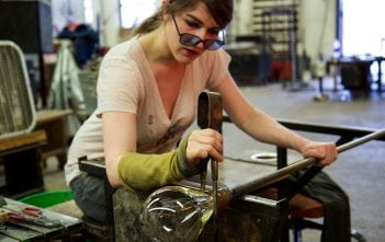 Glass becomes pliable at 2,200 degrees and hardens quickly as it cools into its new shape. Above, glass artist and Appalachian Center for Craft graduate Lyla Nelson molds a piece as it cools. She now has her own glassblowing studio in Pennsylvania.