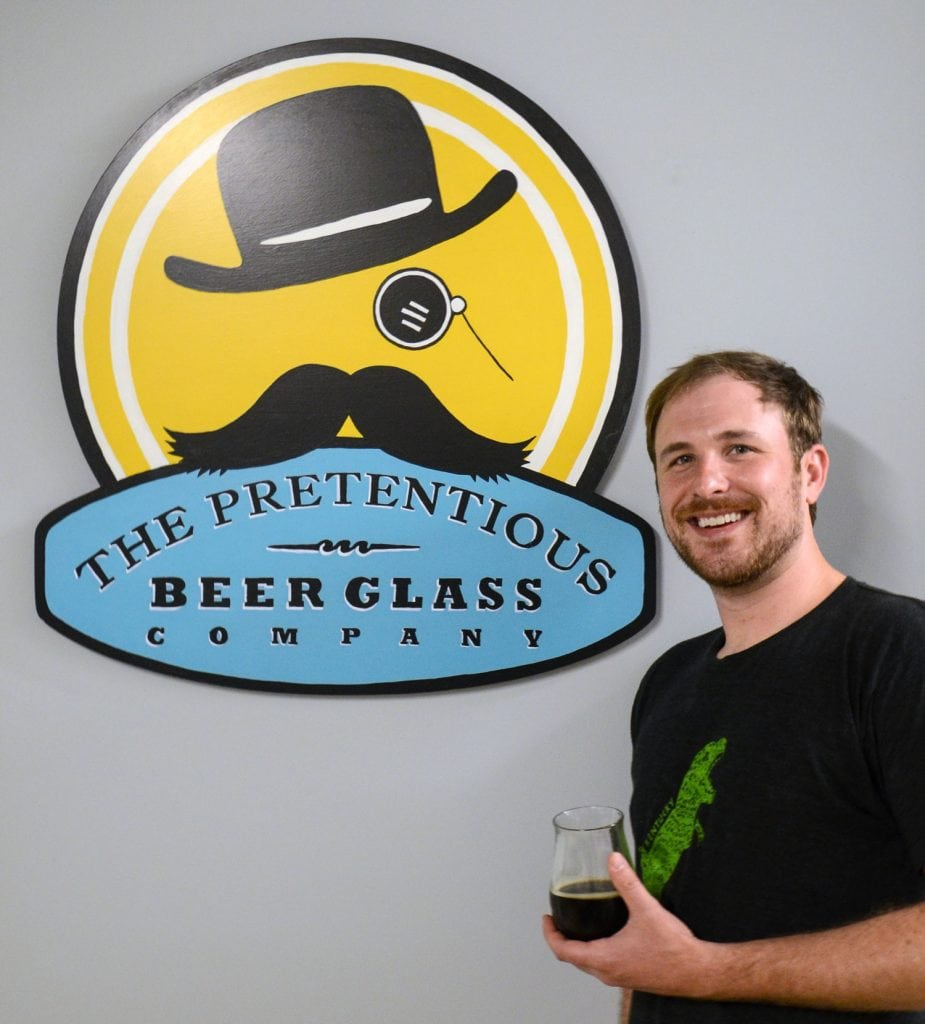 Matthew Cummings holds one of the products he makes for the glass company he founded to serve the growing craft beer industry. Photo courtesy of Matthew Cummings