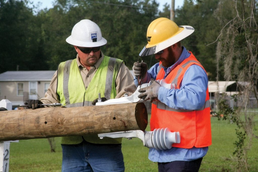 Troy Mitchell of Fayetteville Public Utilities and Cole Woods of Clay Electric Cooperative attach insulators to a new utility pole. (Photograph by Kathy Richardson.)