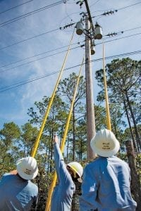 Middle Tennessee EMC linemen help to restore power to Clay Electric Cooperative members in Palatka, Florida. Linemen use hot sticks to reenergize three transformers.